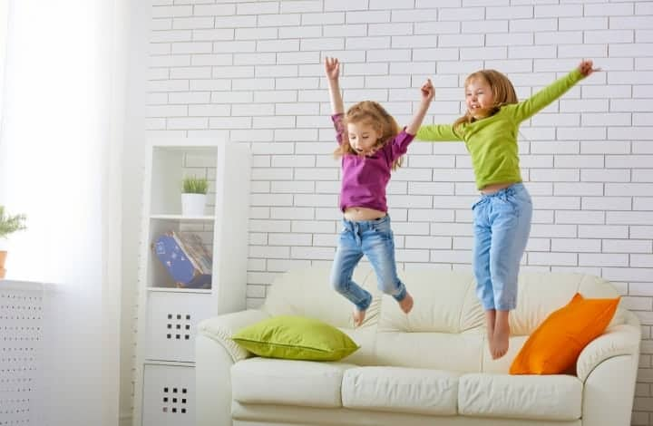 Two girls jumping on a couch