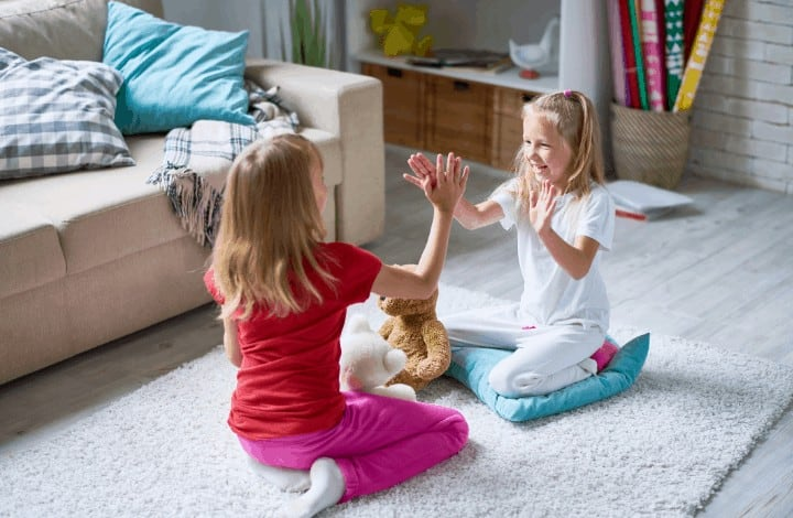 Kids playing hand clapping games on living room floor