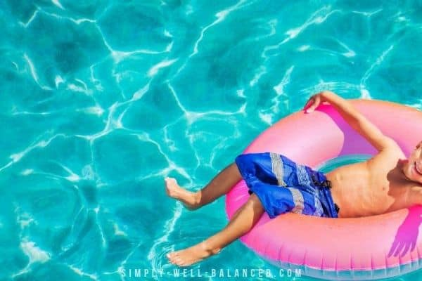 Young boy floating on a blow up toy in pool.