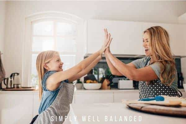 Mom giving daughter a high five in the kitchen