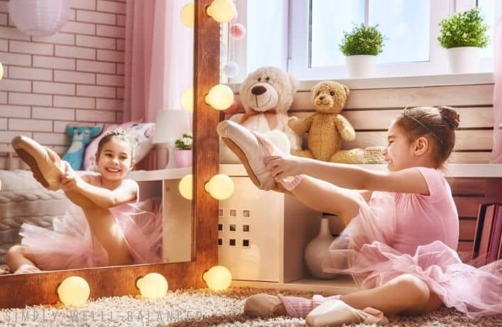Gifts for girls who love to dance. Little girl looking in mirror trying on new ballet shoes