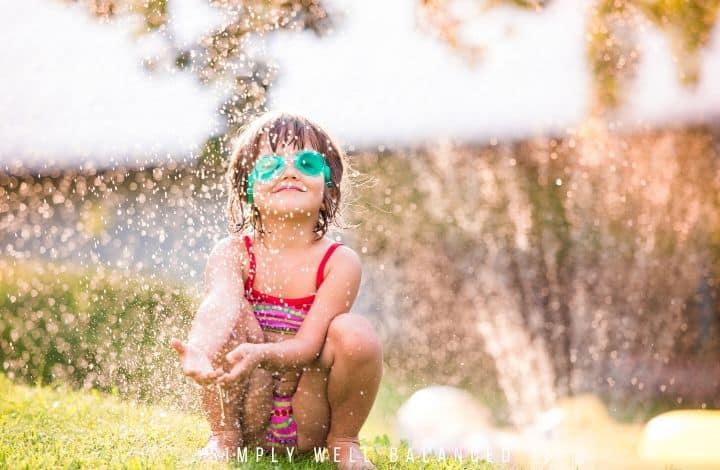 Little girl playing in backyard sprinkler