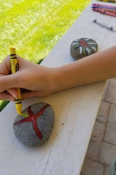 Child using crayon to draw on warm rocks. Melted crayon rocks craft.