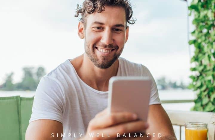 Man reading good morning text message from wife on his cell phone with a smile.