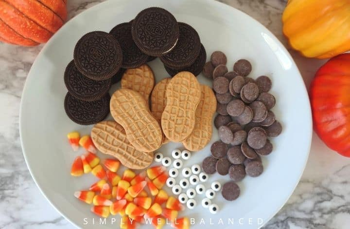 Ingredients for Nutter Butter Turkey Cookies. Nutter butters, oreos, candy corn, candy eyes and candy melts on a plate.