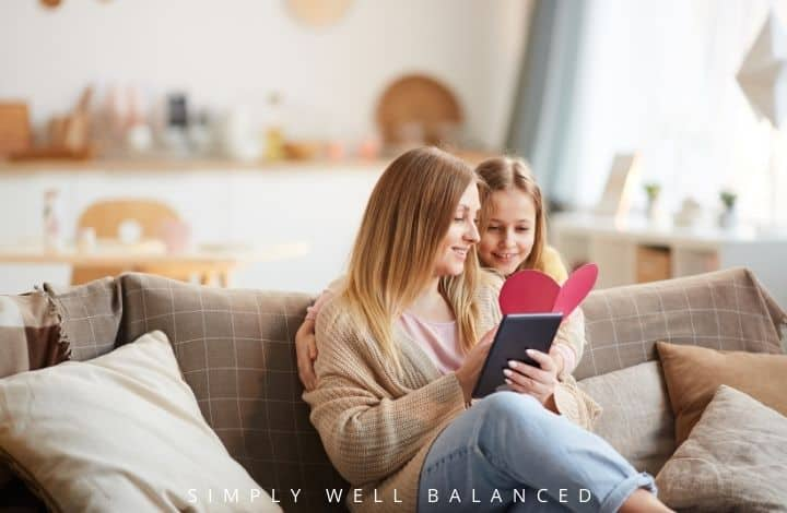 Mother and daughter reading a book and looking at Valentine's: