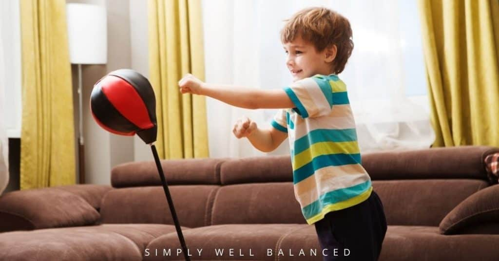 Toddler using a punching bag in the living room